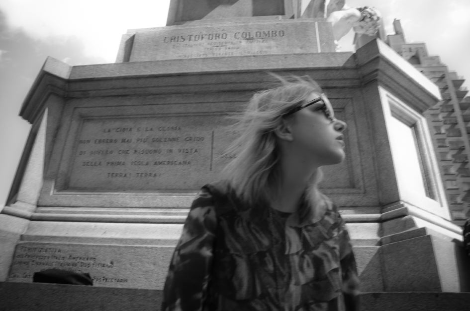 black and white photo of writer, blogger, stylist editor Bunny Bisous Julia Frakes sitting in front of  Cristoforo Colombo Statue & Monument