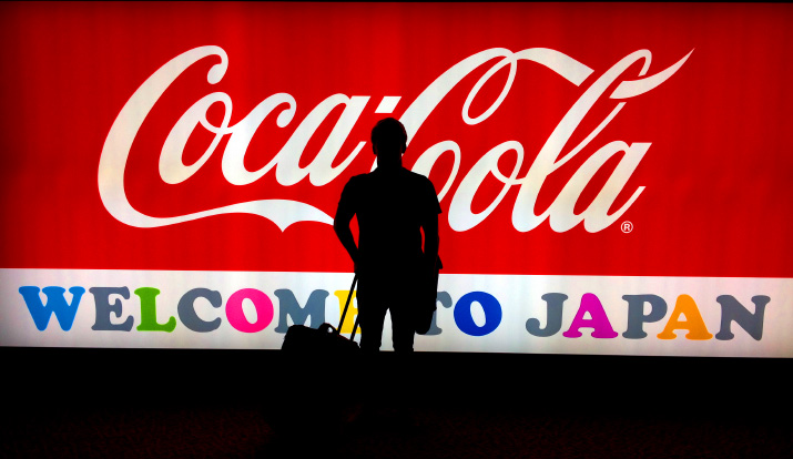 A iphone photo of david roberts silhouette in Front of the Welcome to Japan Coca-Cola Sign