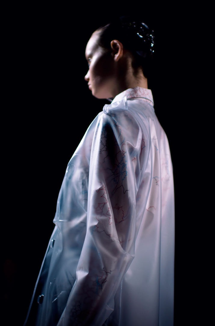 Fashion Artist Danny Roberts Photo of the profile of a model walking in a Clear Anrealage dress raincoat in the Collection from Tokyo Fashion Week 2012