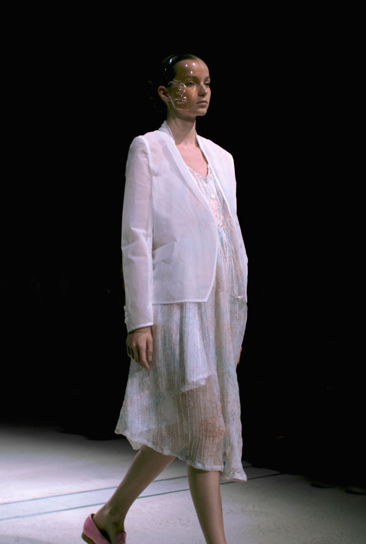 Fashion Artist Danny Roberts Photo of the profile of a model walking in a white body suit like Anrealage a white transparent coat with a white transparent with little print dress with a bubble mask in the Collection from Tokyo Fashion Week 2012