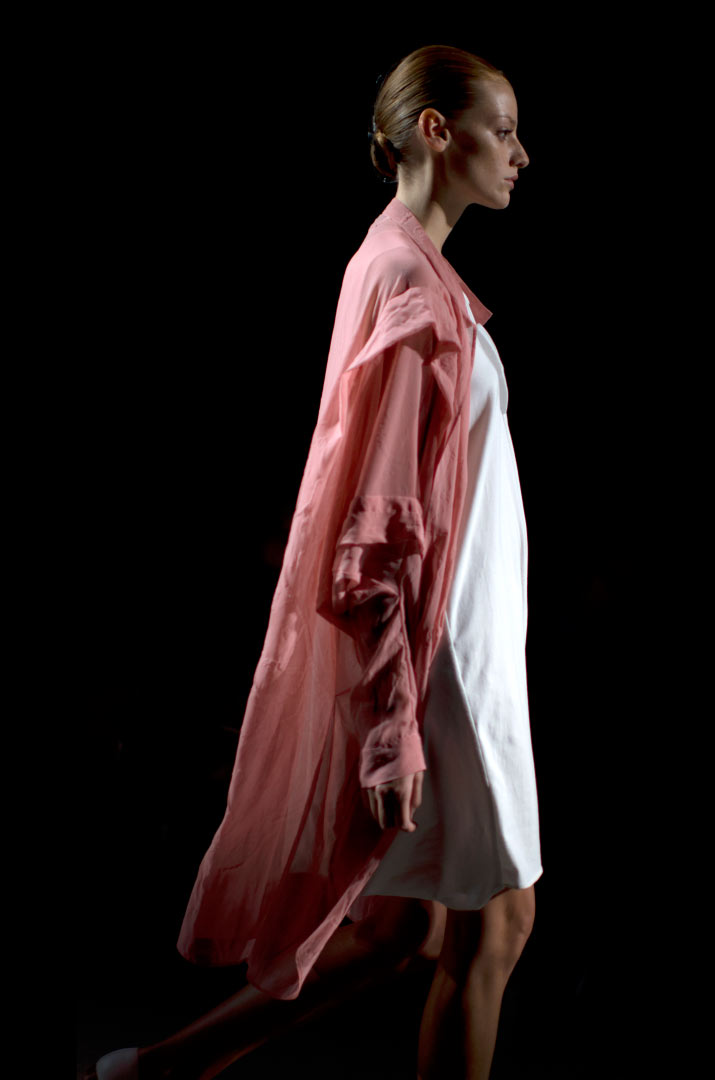Fashion Artist Danny Roberts Photo of the profile of a model walking in a Soft Pink Overcoat with a white Anrealage dress in the Collection from Tokyo Fashion Week 2012