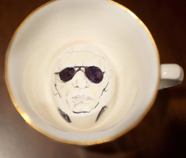 A color photo of karl lagerfeld drawn onto a eggs by artist danny roberts sitting in a cup